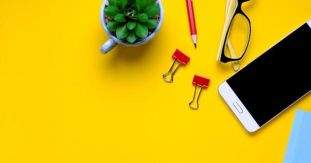 Bril, mobiele telefoon, bloem, stickers, paperclips, briefpapier op een gele achtergrond. werkplek freelancer, zakenman, ondernemer. banier Premium Foto