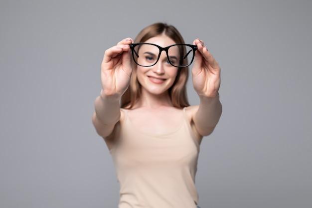 Bril - opticien die brillen toont. close-up van glazen, met glazen en frame in focus. vrouw op grijze muur. Gratis Foto