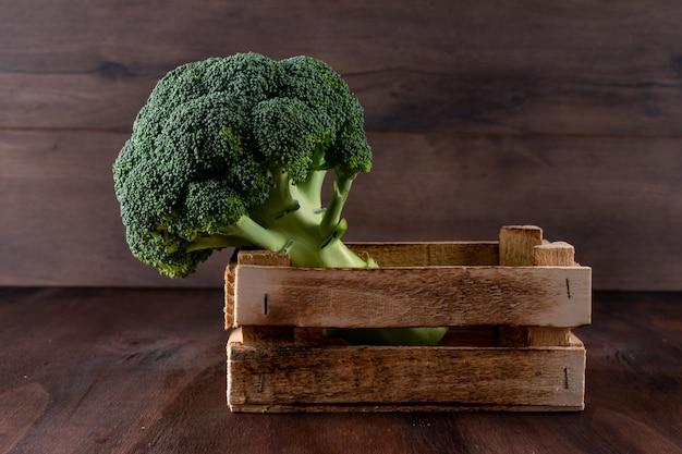 Broccoli in een houten doos verse groente op houten oppervlak Gratis Foto