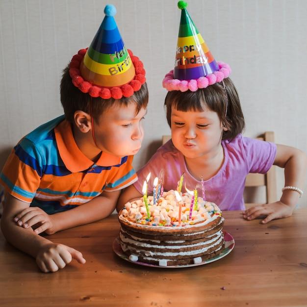 Broer en zus eten een verjaardagstaart met kaarsen uitblazen en knuffelen. Premium Foto