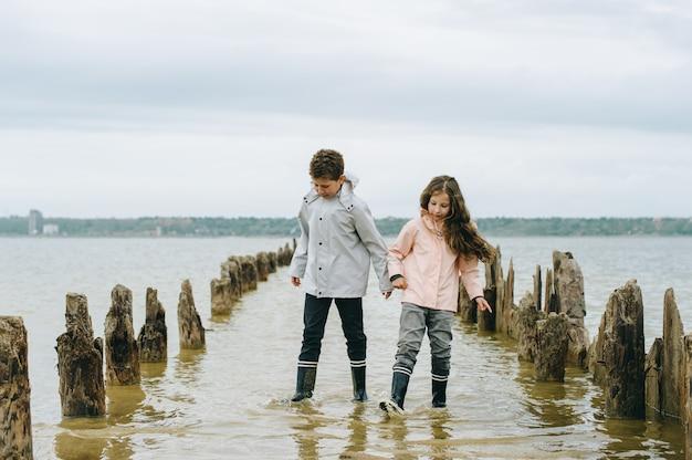 Broer en zus hebben plezier en spelen in de buurt van de zee Premium Foto