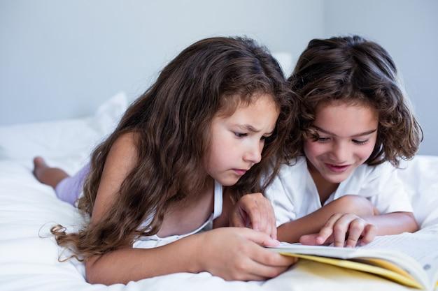 Broer en zus leesboek samen op bed Premium Foto