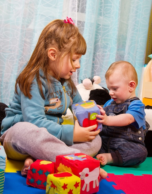Broer en zus spelen met een zachte gekleurde kubus Premium Foto
