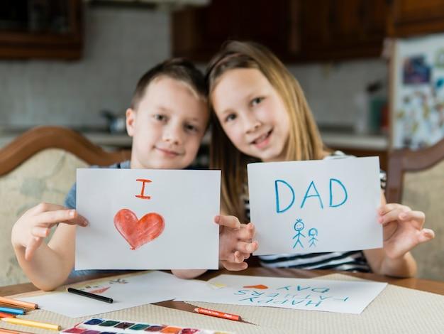 Broer en zus tekenen voor vaderdag Gratis Foto