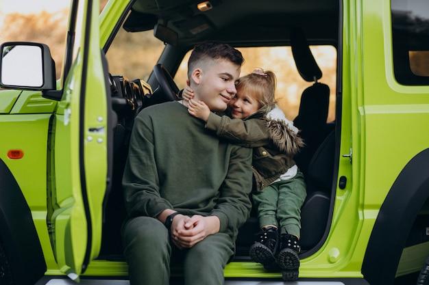 Broer met kleine zusje zit in de groene auto Gratis Foto