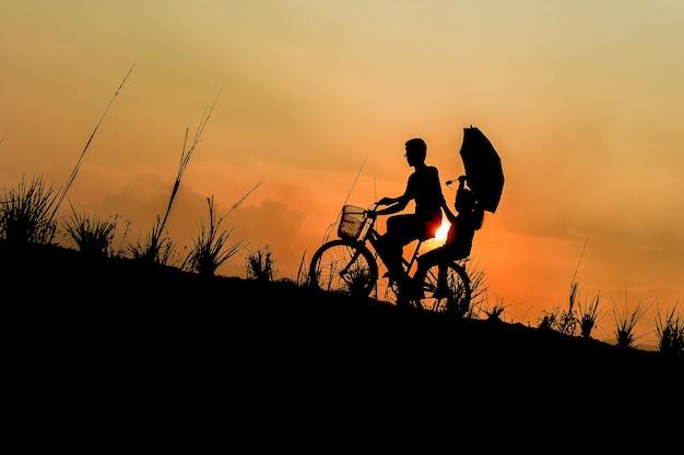 Broer met zus fietsen rijden bij zonsondergang Premium Foto