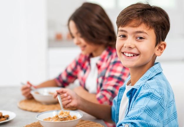 Broers en zussen die van zijaanzichtsmiley ontbijt eten Gratis Foto