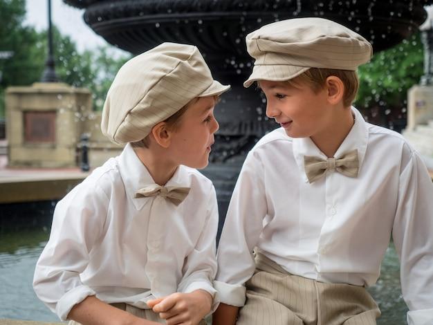 Broers met strikjes en hoeden die op een fontein zitten en elkaar in een park bekijken Gratis Foto