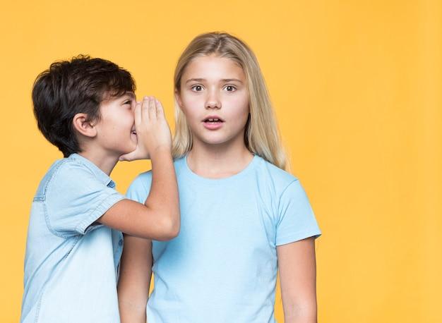 Broertje fluistert geheim tegen zuster Gratis Foto