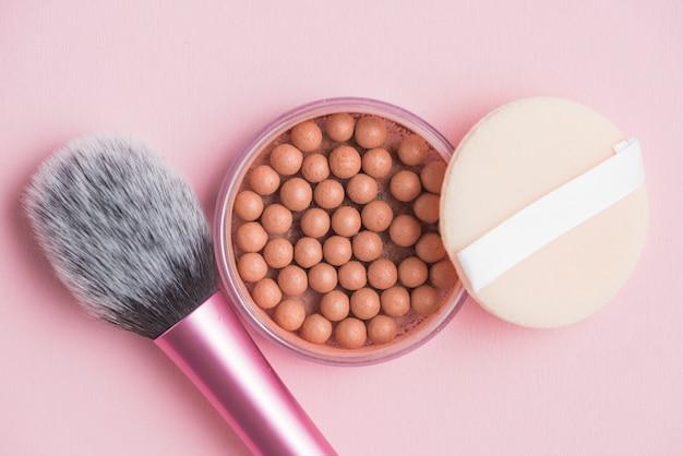 Bronzende parels; spons en make-upborstel op roze achtergrond Gratis Foto