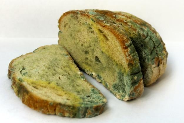 Brood bedekt met schimmel, een stapel bedorven tarwebrood. close-up foto van een patroon van veelkleurige schimmel. Premium Foto