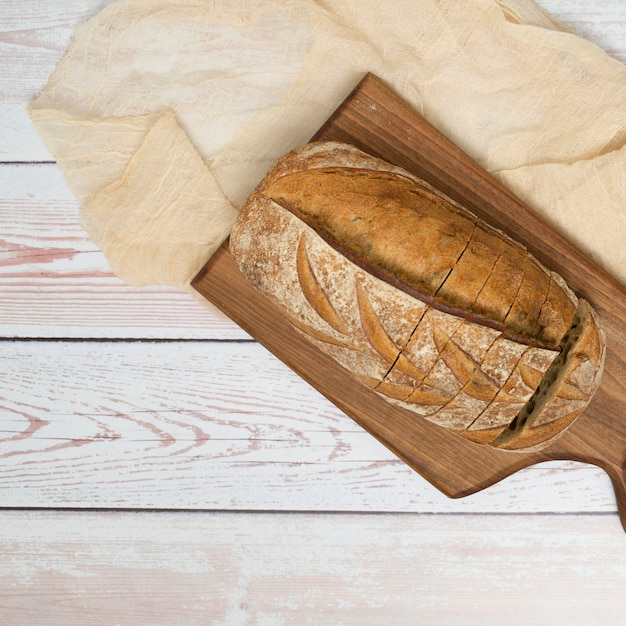 Brood met plakken op hakbord en tafelkleed over het houten bureau Gratis Foto