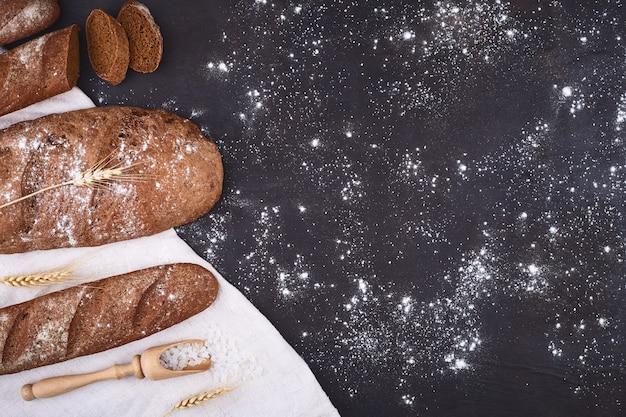 Broodgrens op hout met exemplaar ruimteachtergrond. bruine en witte volkoren broden stillevensamenstelling met tarwe oren verspreid rond. bakkerij en supermarkt voedsel winkel concept. Premium Foto