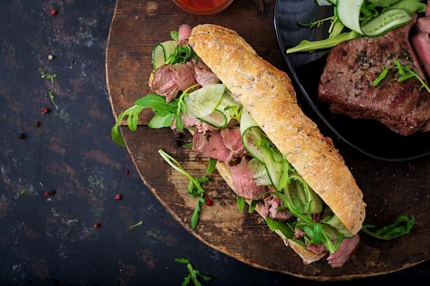Broodje volkorenbrood met rosbief, komkommer en rucola. Premium Foto