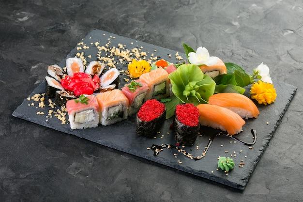 Broodjes en sushi op een zwarte leiachtergrond, japanse keuken Premium Foto