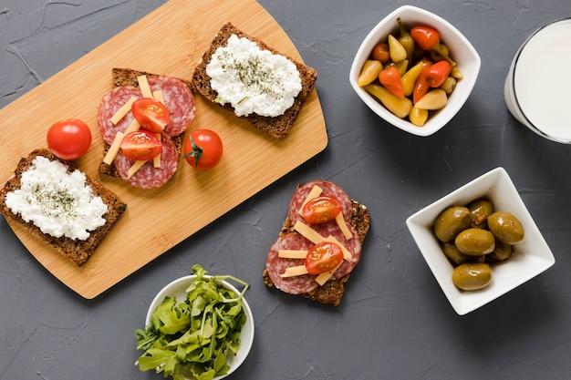 Broodjes op snijplank met olijven Gratis Foto