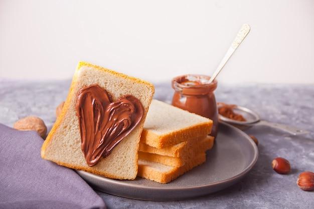 Broodtoast met hartvormige chocoladeroomboter, pot chocoladeroom Premium Foto