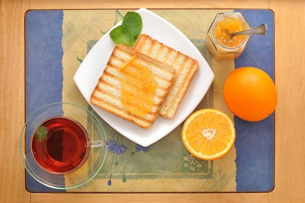 Broodtoast met sinaasappelmarmelade en zwarte thee met munt en sinaasappels Premium Foto