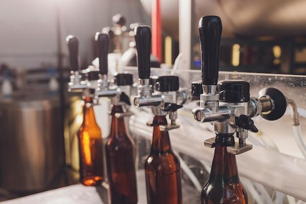 Brouwerijfabriek morsen bier in glazen flessen op transportbanden. industrieel werk, geautomatiseerde productie van eten en drinken. technologisch werk in de fabriek. Premium Foto