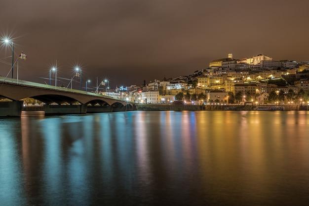 Brug over de zee in coimbra met de lichten die tijdens de nacht in portugal op het water reflecteren Gratis Foto