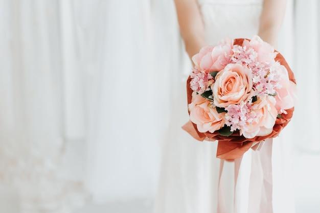 Bruid bedrijf bruiloft boeket in de hand Premium Foto