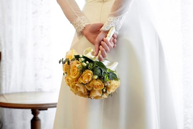 Bruid die een boeket van gele rozen houdt Premium Foto