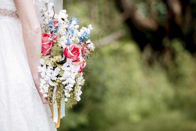 Bruid die het boeket bloemen achter haar houdt Gratis Foto