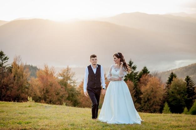 Bruid en bruidegom bij zonsondergang romantisch echtpaar Premium Foto