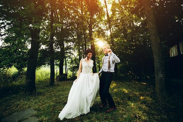 Bruid en bruidegom dansen in de natuur, ergens in het bos Gratis Foto