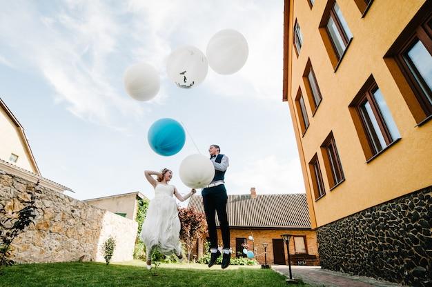 Bruid en bruidegom houden ballonnen in handen en springen. Premium Foto
