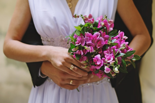 Bruid en bruidegom houden paars rustiek eenvoudig boeket samen in handen. zonnige, heldere foto met trouwringen en armen. witte elegante jurk en diepblauw trouwpak. Premium Foto