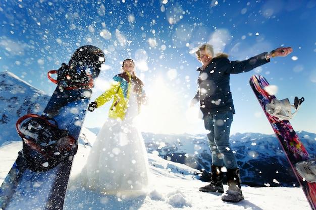 Bruid en bruidegom in liefde gooien sneeuwachtergrond van de alpen courchevel Gratis Foto