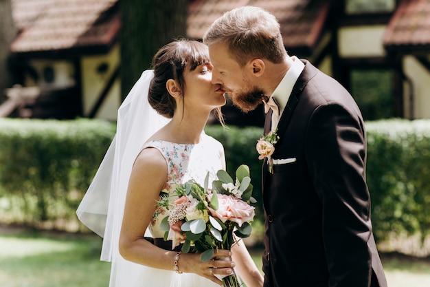 Bruid en bruidegom kijken elkaar aan, knuffelen en zoenen Premium Foto