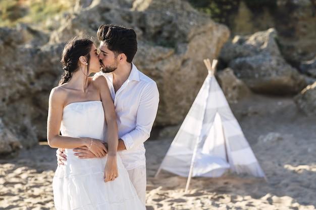 Bruid en bruidegom kussen elkaar op het strand Gratis Foto
