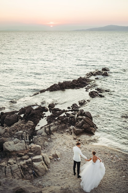 Bruid en bruidegom lopen naar de zonsondergang over de zee Gratis Foto