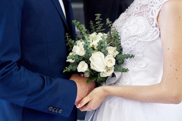 Bruid en bruidegom met een mooi huwelijksboeket bij de ceremonie Premium Foto