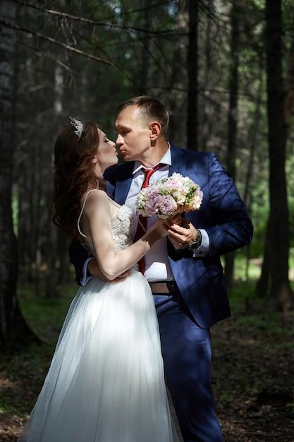 Bruid en bruidegom omarmen en kussen in het donkere bos in de zon. bruiloft in de natuur, portret van een paar verliefd in het park Premium Foto