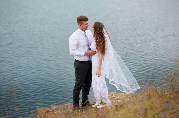 Bruid en bruidegom omarmen op het meer voor een wandeling Premium Foto