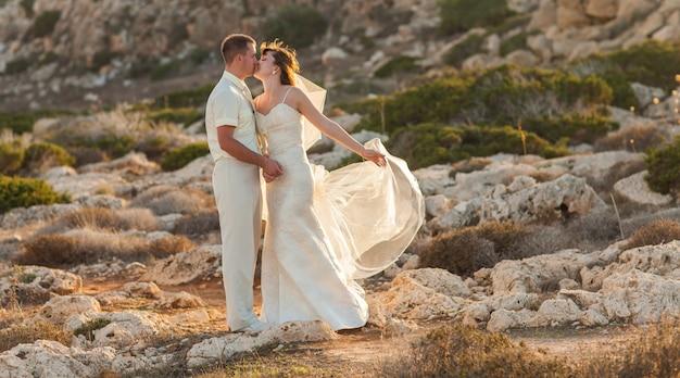 Bruid en bruidegom op een romantisch moment op de natuur. stijlvolle bruidspaar buitenshuis Premium Foto