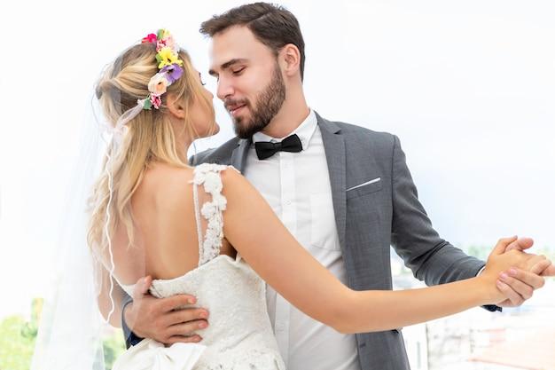 Bruid en bruidegom paar van kaukasische dansen en grapje in trouwstudio. Premium Foto