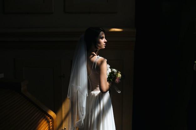 Bruid en bruidegom poseren in de slecht verlichte kamer Gratis Foto
