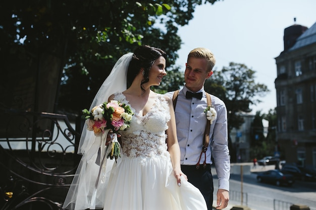 Bruid en bruidegom poseren in de straten van de oude stad Gratis Foto