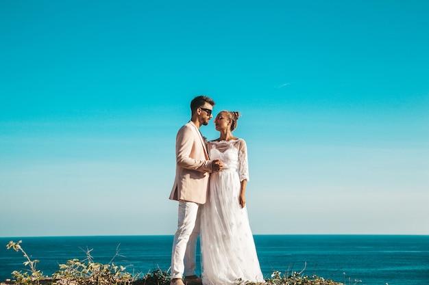Bruid en bruidegom poseren op de klif achter blauwe hemel en zee Gratis Foto
