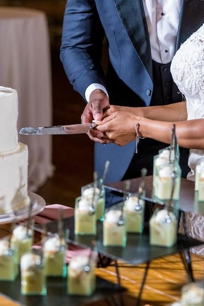 Bruid en bruidegom snijden de mooie witte bruidstaart Gratis Foto