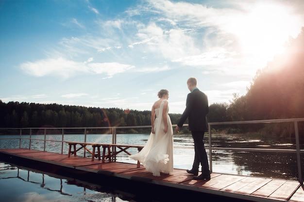 Bruid en bruidegom staan op de brug aan het meer. het stel pasgetrouwden Premium Foto