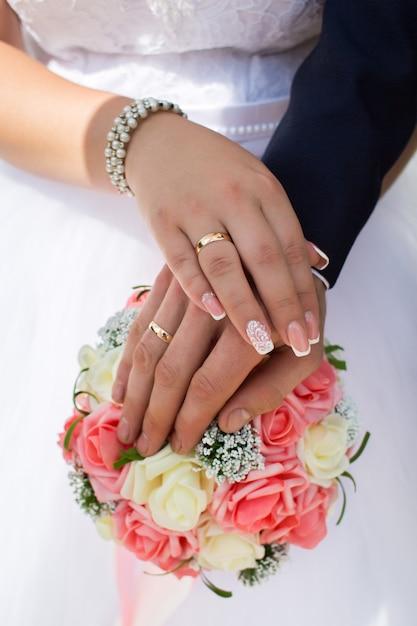 Bruid en bruidegom tonen hun trouwringen op de achtergrond van het boeket Premium Foto