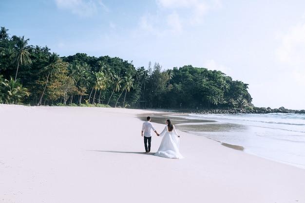 Bruid en bruidegom wandelen op het strand Premium Foto