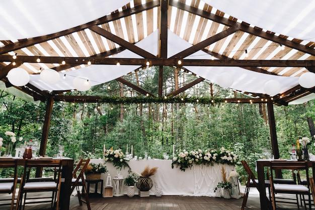 Bruid en bruidegomlijst met bloemen en lichten in de modieuze trefpunt van het bohohuwelijk wordt verfraaid dat Premium Foto