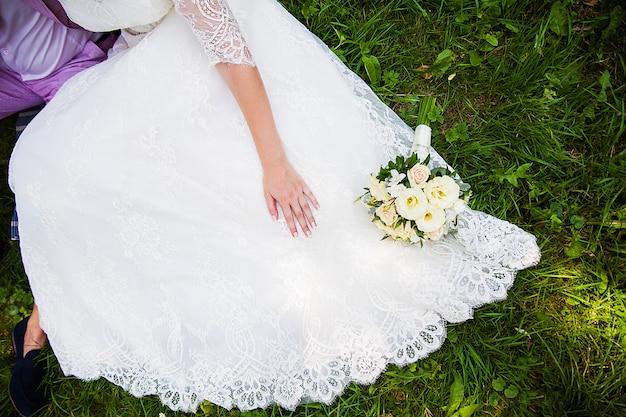 Bruid en bruidegomzitting op gras met mooi boeket Premium Foto