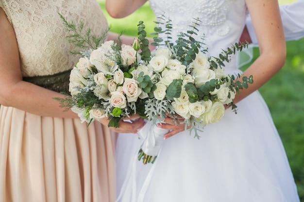Bruid en bruidsmeisje met boeketten op huwelijksgang in park Premium Foto